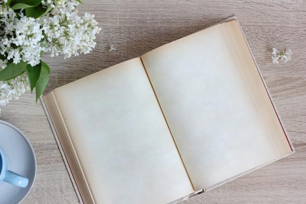 Открытая книга с пустыми страницами на столе, вид сверху. плоская планировка. место для вашего текста.
