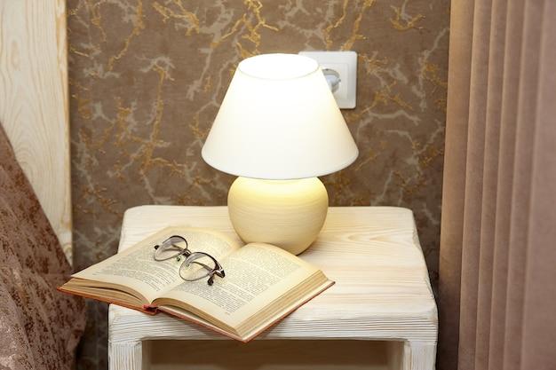 常夜灯の光で床下のベッドサイドテーブルに眼鏡をかけた開いた本。