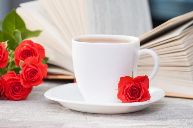 赤いバラとお茶の開いた本。