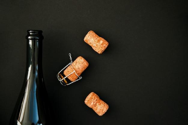샴페인 또는 검정색 배경에 와인 한 병을 엽니 다. 병의 코르크가 그 옆에 놓여 있습니다. 휴일을위한 음료. 배경과 질감.
