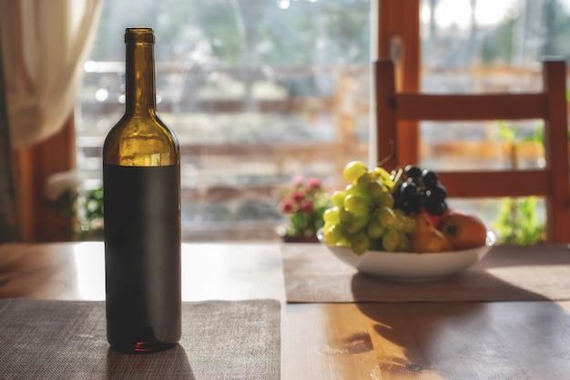 Открытая бутылка красного вина и фруктов на столе.