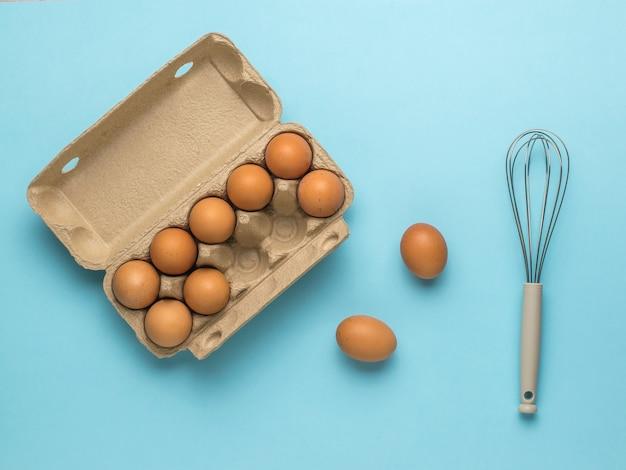 卵の開いた箱と青い背景の泡立て器。天然物および厨房機器。