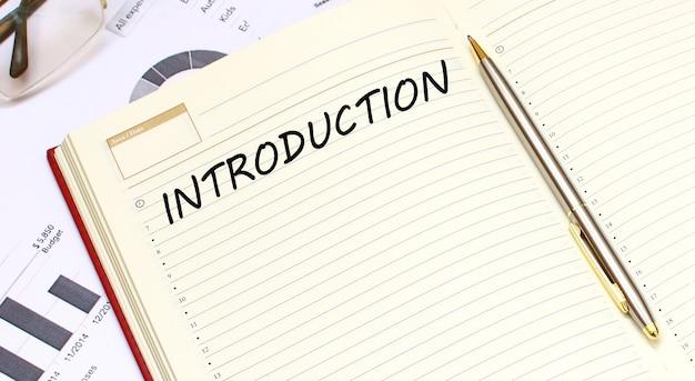 Открытый дневник с текстом лежит на офисном столе с финансовыми диаграммами.