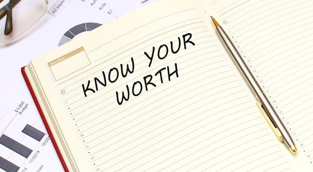 テキスト付きのオープンな日記は、財務チャートのあるオフィスデスクにあります