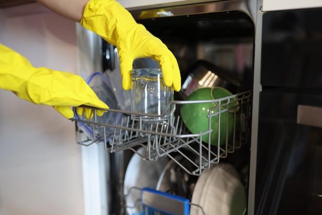 Открытая посудомоечная машина, из которой вынимается чистая посуда
