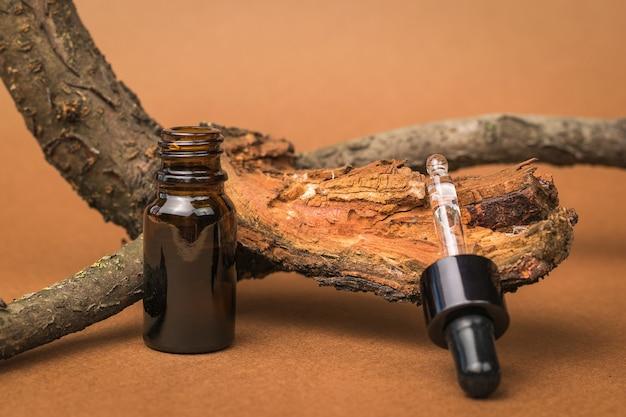 Открытая бутылка-капельница и старое дерево на коричневом фоне. косметика и лекарственные средства на основе природных минералов.