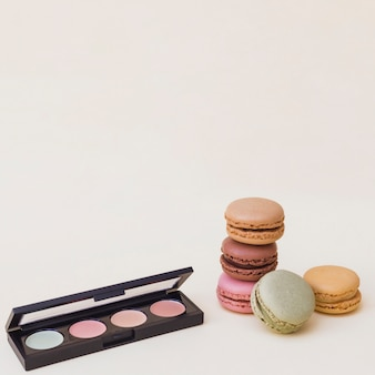 An open eye shadow palette with macaroons on beige background