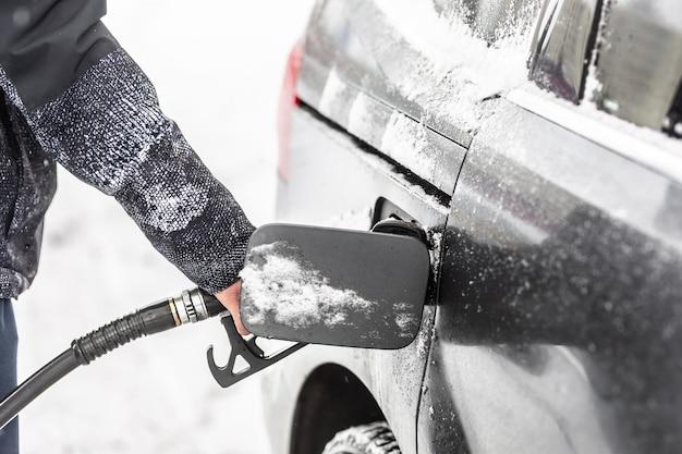 가스 권총이 들어 있는 개방형 연료 탱크는 눈 덮인 겨울에 남성을 안고 있었습니다.