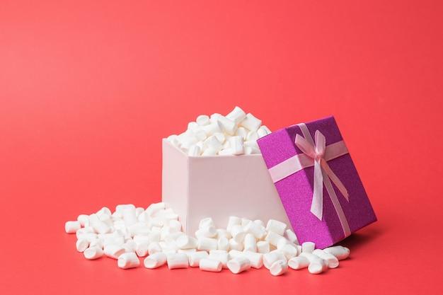 Открытая подарочная коробка, переполненная зефиром. сладкое угощение.