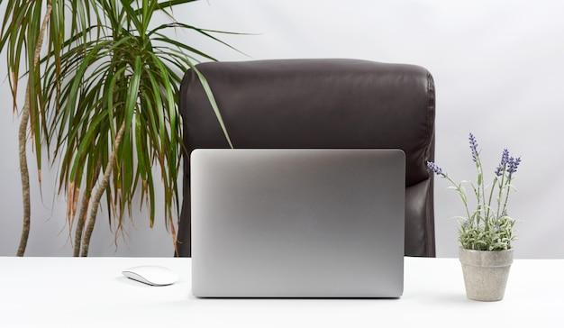 オープングレーのラップトップは、ワイヤレスマウス、フリーランサー、ビジネスマンの職場の横にある白いテーブルの上に立っています。