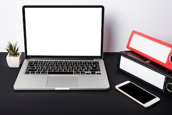 An open laptop with blank white screen; cell phone and paper clips on black desk against white wall