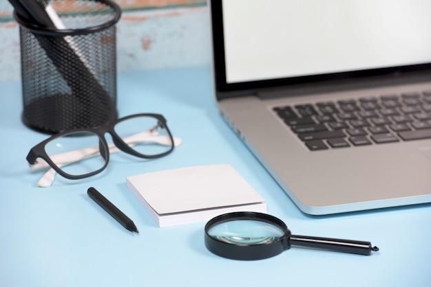 Открытый ноутбук с увеличительным стеклом; клейкие заметки; ручка; очки на синем деревянном столе