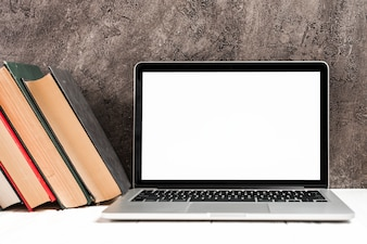 An open laptop with old hardcover antique books on desk against concrete wall