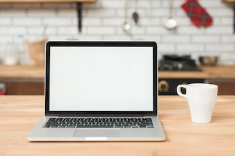 An open laptop with white blank screen and cup of coffee on wooden table in the kitchen