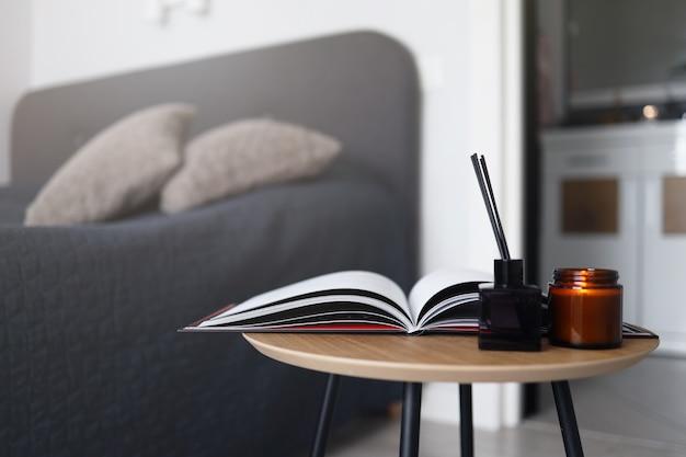 キャンドルと寝室のアロマディフューザーを備えたコーヒーテーブルのオープンマガジン。ホーム居心地の良い写真。