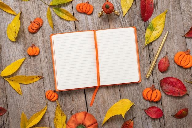 Открытый блокнот лежит на столе с опавшими листьями