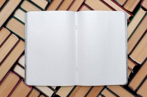 Открытый блокнот лежит на книгах