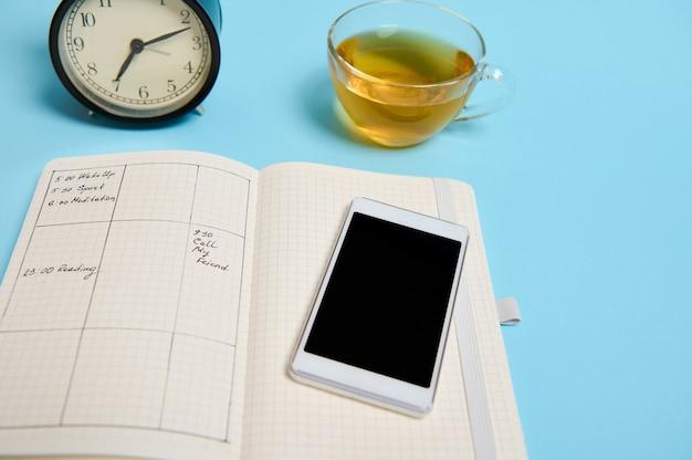 일정, 스마트폰, 유리 컵, 검은색 알람 시계가 있는 열린 노트북이 파란색 표면에 놓여 있습니다. 텍스트 복사 공간이 있는 배경색입니다. 시간 관리, 마감 및 일정 개념