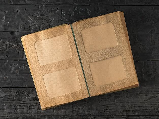 Открытый старый фотоальбом на темном деревянном столе. предмет семейных ценностей. вид сверху. плоская планировка.
