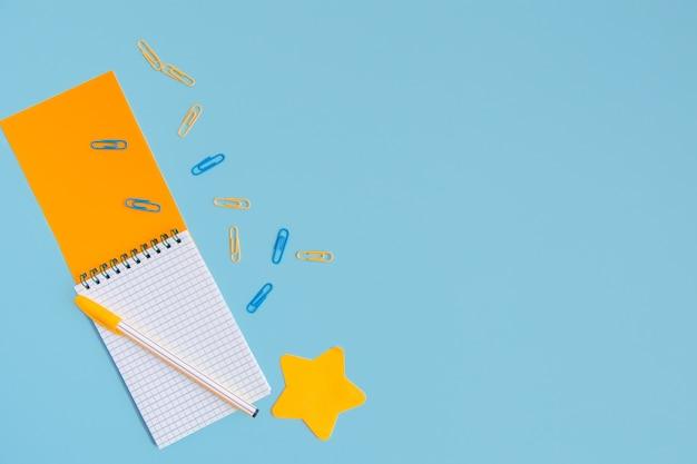 ペン、星型のステッカー、青い背景に散らばったペーパークリップが付いた開いたオレンジ色のメモ帳。コピースペースのあるフラットレイアウト