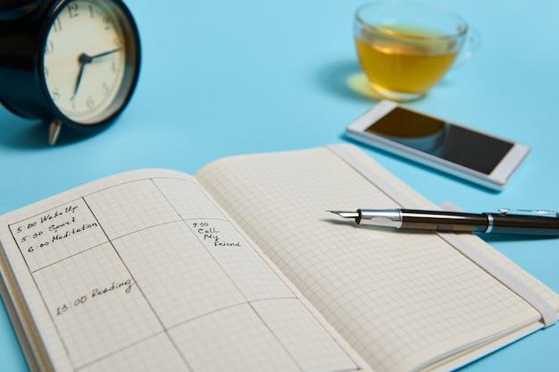 일정, 스마트폰, 잉크 펜, 차 한 잔, 검은색 알람 시계가 있는 개방형 주최자가 파란색 표면에 있습니다. 복사 공간이 있는 배경색입니다. 시간 관리, 마감일, 일정 개념