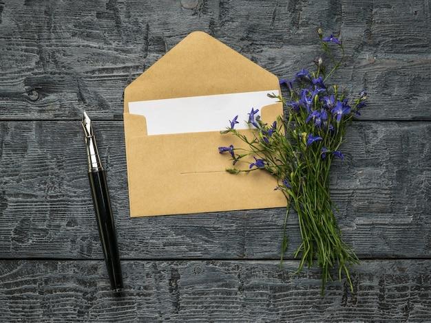 木製のテーブルに一枚の紙、万年筆、花の花束が入った開いた郵便封筒。フラットレイ。