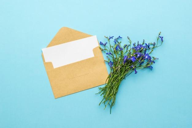 紙のシートと青い背景に野生の花の花束と開いた郵便封筒。愛の対応の概念。フラットレイ。