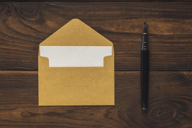 Открытый почтовый конверт с листом бумаги и перьевой ручкой на деревянном фоне. плоская планировка.
