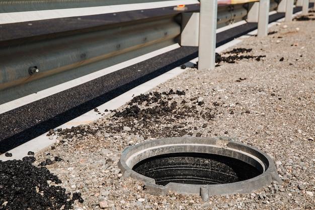 Открытый люк канализации, представляющий опасность для людей, идущих по улице города ремонтные работы