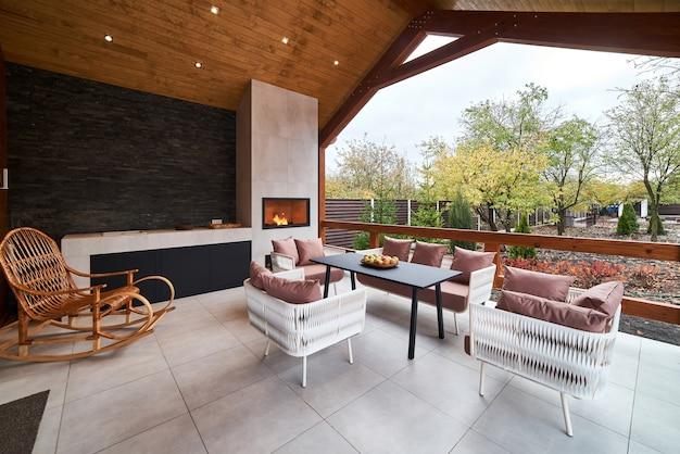 Открытая терраса со столом, стульями, камином и яблоками.