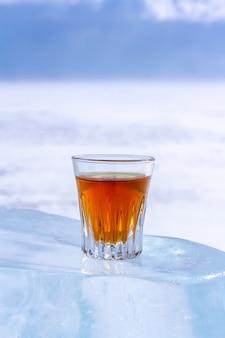 グラスに入ったオレンジ色のアルコール飲料が氷の上に立っています。氷は太陽の下で溶けた。明るいぼやけた背景。スペースをコピーします。側面図。垂直。