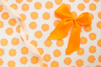 An orange bow and curled ribbon on floral gift paper