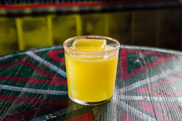 Апельсиновый коктейль в рок-бокале с большим кубиком льда и острым ободком на бокале.