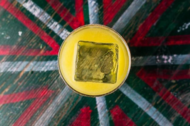 Апельсиновый коктейль в бокале с большим кубиком льда, вид сверху
