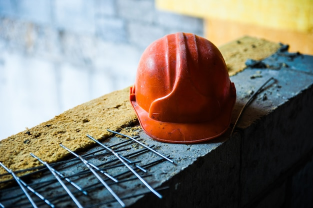 Оранжевый шлем строителя лежит на кирпичной кладке на стройплощадке