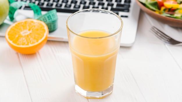 オレンジジュースと白い木製の机の上のノートパソコン