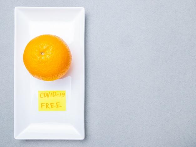 オレンジは、白い長方形のセラミックプレート内の青い医療マスクの上にあります