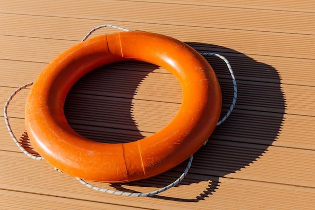 Оранжевый спасательный круг лежит на потрескавшемся фоне концепции безопасности воды