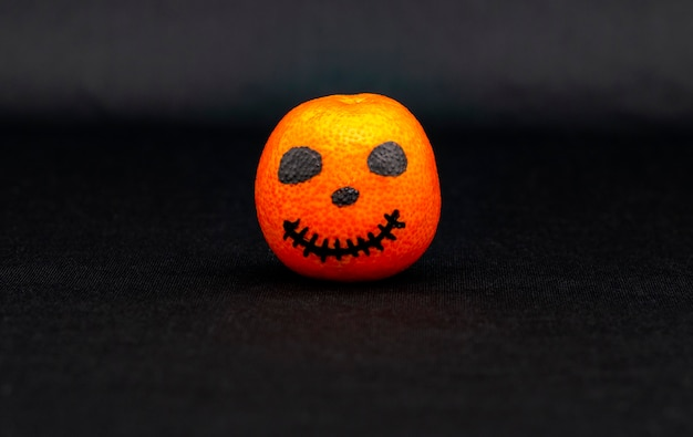 Оранжевый мандарин, раскрашенный как тыква на хэллоуин