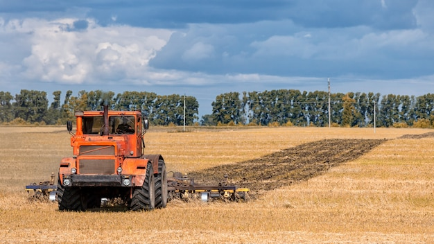 Оранжевый современный трактор пашет землю в золотом поле пшеницы в летний день