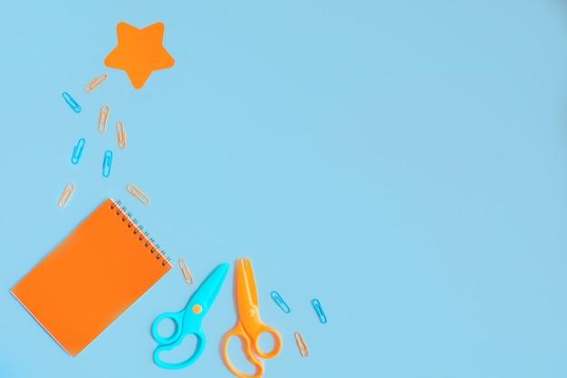 オレンジ色のメモ帳、はさみ、星型のステッカー、青い背景に散らばったペーパークリップ。コピースペースのあるフラットレイアウト