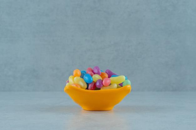 흰색 표면에 화려한 젤리 콩 사탕의 주황색 접시