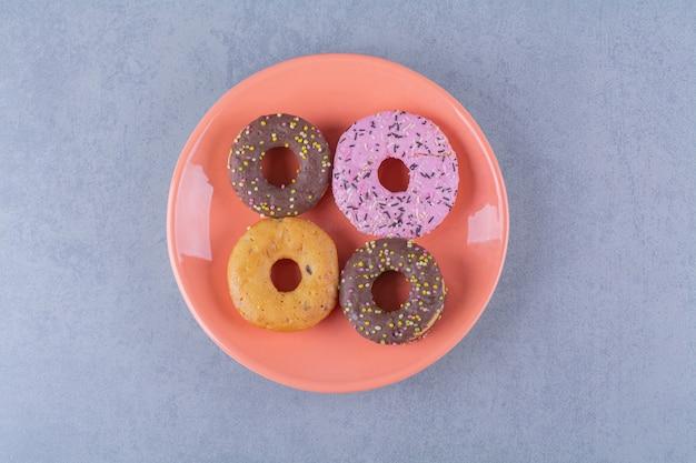 스프링클이 있는 맛있는 초콜릿 도넛의 오렌지 플레이트.