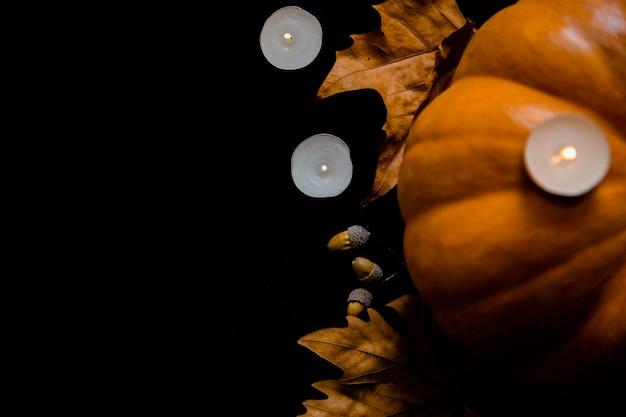 검정색 배경에 나뭇잎, 도토리, 촛불이 있는 주황색 호박. 고품질 사진
