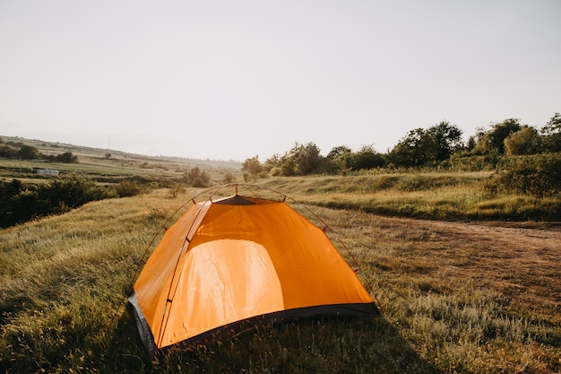 Оранжевая палатка на лугу в горах.