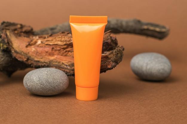 Оранжевая трубка из сливок, старого дерева и камней на коричневом фоне.
