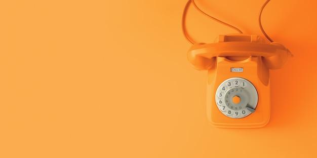 オレンジ色の背景を持つオレンジ色のビンテージダイヤル電話。