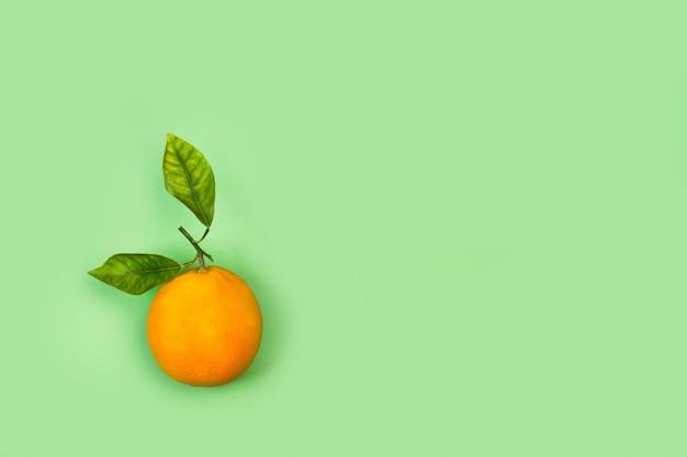 Апельсин с листьями на зеленом фоне