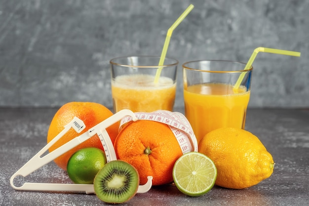 Апельсин, обернутый измерительной лентой и штангенциркулем, окруженный свежими фруктами, стаканами сока и смузи на сером бетонном фоне. концепция похудения, приведения фигуры в форму.