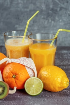 오렌지는 회색 콘크리트 배경에 신선한 과일과 주스 및 스무디 잔으로 둘러싸인 캘리퍼스와 측정 테이프로 싸여 있습니다. 슬리밍의 개념은 그림을 모양으로 만듭니다.